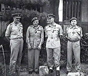 Full-length outdoor portrait of four men in light-coloured military uniforms