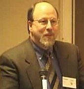 A middle-aged man with balding blond hair, a white beard, and glasses stands beside a microphone in his grey suit and pattern tie.