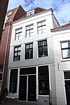foto van Bedrijfspand met twee verdiepingen en afgeknot schilddak. Gepleisterde gevel met hijsluiken en houten onderpui met kleine roedenverdeling