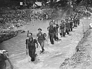 A black-and-white photograph of soldiers marching up a creek. The soldiers have their rifles slung and are knee deep in muddy water