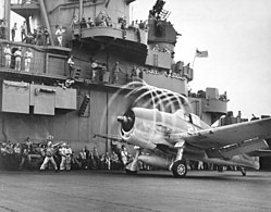 A F6F-3 Hellcat from VF-5 makes condensation rings aboard USS Yorktown (CV-10), 20 November 1943 (520641).jpg