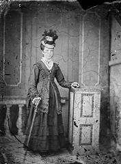 A young woman standing and wearing a hat