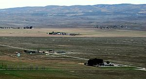 California Valley, California - Aerial view northeast, with community center at lower right next to northern end of runway at right edge. Soda Lake Road is visible running diagonally up toward the left. The main community is about one mile (1.6 km) further south beyond the other end of the runway.