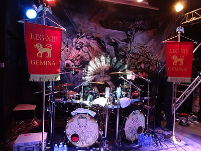 A large metal drum kit with two bass drums. Alestorm, Ex Deo and Lagerstein at St des Seins, Toulouse, 2013-03-20 - Ex Deo flags + drums.JPG