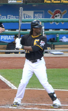 A dark-skinned man in a black baseball jersey and cap, white pants, and white batting gloves stands in a right-handed batting stance.