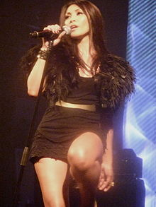 A black-haired woman performing on stage