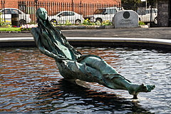 Bronze sculpture of a young woman reclining with legs crossed, in a pool of water