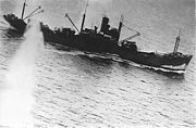 A ship under way, with splashes on both sides.