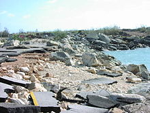 A crumbled roadway at the water's edge