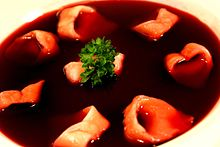 A bowl of clear dark-red broth with small ear-shaped mushroom-filled dumplings