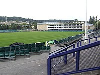 Area of mown grass with rugby posts and a white fronted pavilion building. In the foreground are terraces and seating with hills in the distance.