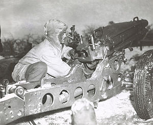 460th Parachute Field Artillery Battalion (United States) - Corporal Tony D'addio of Battery D, 460th Parachute Field Artillery Battalion labors to sight in a 75mm pack howitzer outside Logbierme, Belgium.