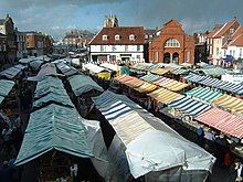 Brightly coloured canvas tops of many market stalls in a town setting.