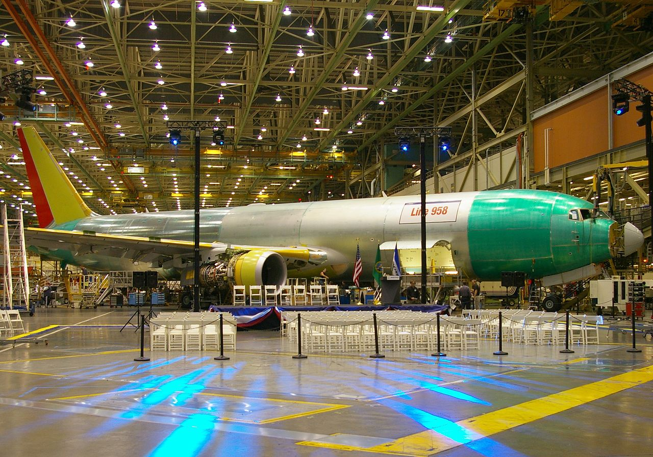 Airplane assembly hall, featuring an unpainted metallic twin-jet aircraft, a presentation podium, and arranged audience chairs.