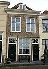 foto van Huis met gepleisterde lijstgevel met stoeppaal