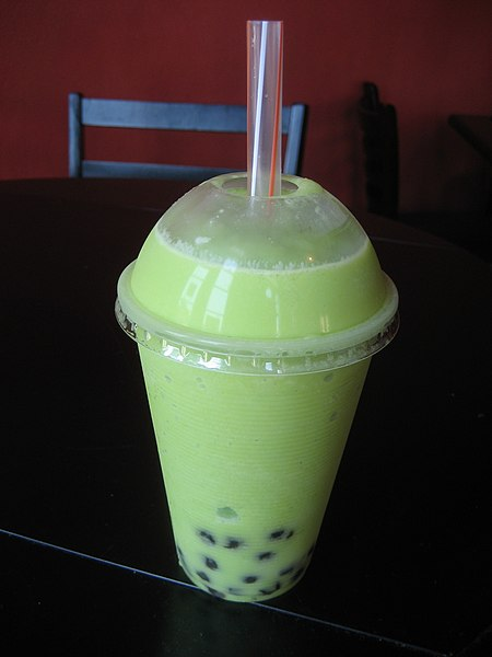 Honeydew bubble tea in a plastic cup with straw