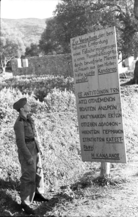 "Bilingual sign erected at the village of Kandanos in Crete, razed in reprisal for the local's armed resistance against invading Germans. The German part of the sign reads: ""Kandanos was destroyed in retaliation for the bestial ambush murder of a paratrooper platoon and a half-platoon of military engineers by armed men and women."" Bundesarchiv Bild 101I-779-0003-22, Griechenland, Schild uber Zerstorung von Kandanos.jpg"