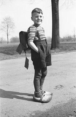 photographie en noir et blanc d'un écolier portant des sabots fourrés par de grosses chaussettes en laine