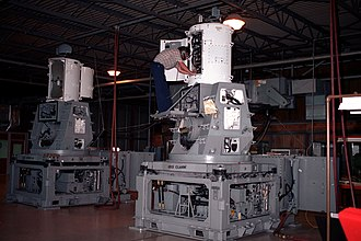 Phalanx CIWS - A technician checks the radar transmitter and microwave assemblies of a Phalanx CIWS, most likely a Block 0. On the unit in the background, the search radar can be seen at the top left with the vertical, orange-peel shaped, tracking radar below it.