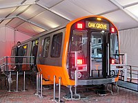 A subway rail car prototype with orange trim sits on a raised platform a tent with stairs to one entrance and a ramp to the opposite entrance