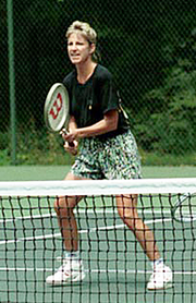 A blonde-haired female tennis player with multi-colored shorts and a black shirt, with the tennis racket out in front of her