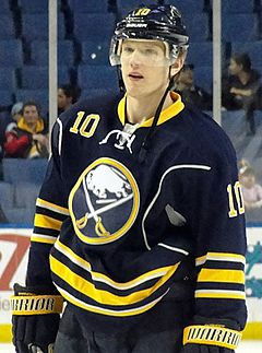 A Caucasian ice hockey player in his late-twenties looking forwards.  He is wearing a blue jersey with green and white trim, as well as a blue, visored helmet.  He holds his hockey stick horizontally across his waist in a relaxed position.