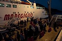 Naufraghi della Costa Concordia in attesa di lasciare l'Isola del Giglio a bordo di un traghetto.