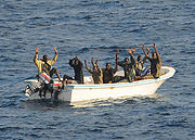 Seven men in a small motor skiff with their hands raised.