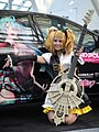 Cosplayer of Kagamine Rin and itasha of Hatsune Miku at Anime Expo 20110701.jpg