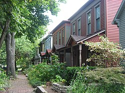 A view of the Cottage Home Historic District from Dorman Street. Two historic homes and a historic sidewalk can be seen.