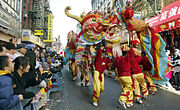 Several men in red and yellow outfits carry a colorful paper dragon in the street while onlookers watch behind police barriers.