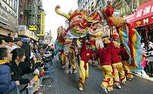 Vários homens em trajes vermelhos e amarelos carregam um dragão de papel colorido na rua, enquanto os espectadores assistem atrás das barreiras policiais.