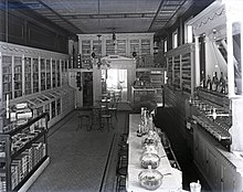 A black and white photograph of the interior of an unidentified drugstore. A large cigar counter and a long bar with seating is featured. The photo was taken by Charles F. Mensing around 1900. The photo is a glass plate negative.