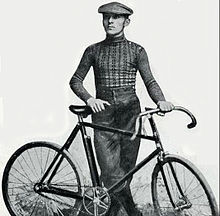 A man posing with a bike.