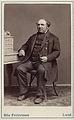 En man poserar sittande vid ett skrivbord. Från Saxtorp, Harjagers härad i Skåne - Nordiska Museet - NMA.0042844.jpg