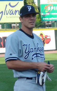 A man in a grey uniform and a navy blue hat holds a pair of white batting gloves.