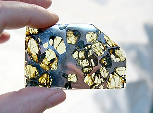 "A slice of the Esquel pallasite, clearly showing the large <a href=""http://search.lycos.com/web/?_z=0&amp;q=%22olivine%22"">olivine</a> crystals suspended in the metal <a href=""http://search.lycos.com/web/?_z=0&amp;q=%22Matrix%20%28geology%29%22"">matrix</a>."