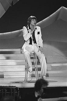 Fotografia in bianco e nero di Johnny Logan che si esibisce sul palco del concorso del 1980
