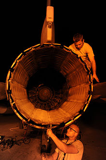 View of engine exhaust nozzle as two maintenance crew inspecting and repairing an F-16 engine at night