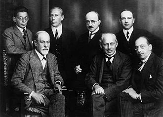 "Ernest Jones - The ""Committee"", 1922. Left to right, seated: Sigmund Freud, Sándor Ferenczi, and Hanns Sachs.  Standing; Otto Rank, Karl Abraham, Max Eitingon, and Ernest Jones."