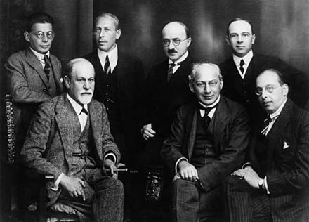 "The ""Committee"", 1922. Left to right, seated: Sigmund Freud, Sandor Ferenczi, and Hanns Sachs. Standing; Otto Rank, Karl Abraham, Max Eitingon, and Ernest Jones. Freud and other psychoanalysts 1922.jpg"