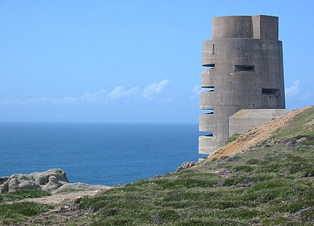 As part of the Atlantic Wall, between 1940 and 1945 the occupying German forces and the Organisation Todt constructed fortifications round the coasts of the Channel Islands, such as this observation tower at Les Landes, Jersey. German World War II tower Jersey.jpg