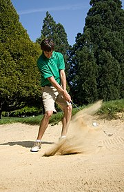 A golfer hits a ball from a bunker.