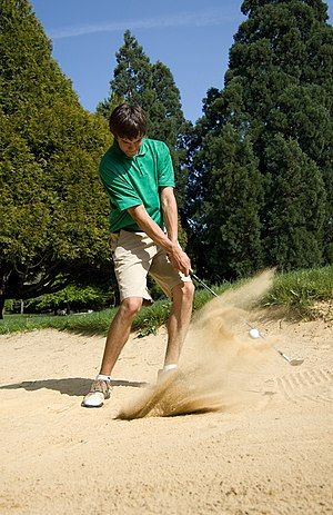 English: A golfer hits out of a green-side bunker.