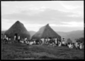 Group of local men, women and children, by thatched buildings, probably Fiji ATLIB 517536.png