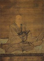 Seated monk holding a rosary in three-quarter view.