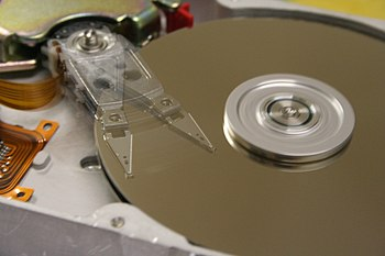 The inside of a hard disk displaying the read/write head traveling over the top platter.