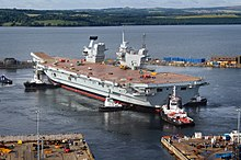 A Queen Elizabeth-class aircraft carrier docked in Scotland. This ship is one of two planned aircraft carriers and will soon make its way to Portsmouth Harbour, its home port.
