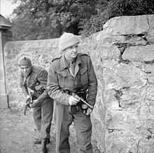 Two men in uniforms advance behind a wall carrying weapons