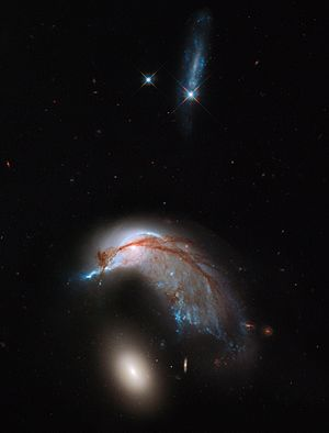 This image shows the two galaxies interacting. NGC 2936, once a standard spiral galaxy, and NGC 2937, a smaller elliptical, bear a striking resemblance to a penguin guarding its egg.